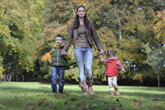 Mother and children walking in the park Royalty Free Stock Image