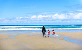 Mother and children are walking on sandy Atlantic beach. Family walking on a beach on vacations in warm clothes. Panoramic landscape picture Royalty Free Stock Image