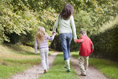 Mother and children walking on woodland path Stock Images