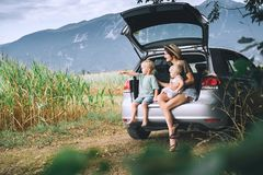Mother and children watching on countryside. Family in road trip. Mother and children sitting in an open car trunk and watching on nature and countryside. Family stock photo
