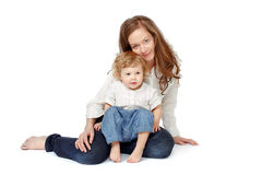 Mother with children on a white background. Mom sitting on his lap with the baby, caring, in jeans on a white background stock photo
