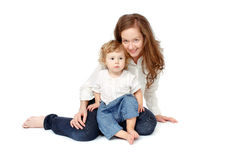 Mother with children on a white background. Mom sitting on his lap with the baby, caring, in jeans on a white background Stock Photos