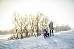 Mother and children on winter vacation. Enjoying snow day on sleigh Royalty Free Stock Image