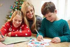 Mother And Children Writing Letter To Santa Together. Happy Mother And Children Writing Letter To Santa Together At Home Stock Photos