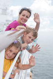 Mother with childrens stand on deck of ship. Mother with her childrens stand on deck of large passenger ship near handrails and waving their hands, focus on Stock Photos