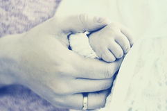 Mother holding her babies hand. High key close up of a mother holding the hand of he newborn baby Royalty Free Stock Images
