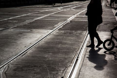 Mother and childwith bicycle crossing the street. Silhouette of Mother and child with a bicycle crossing a desert street with rails on the asphalt royalty free stock photography
