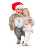 Mother in Christmas hat and baby holding clock Stock Photos