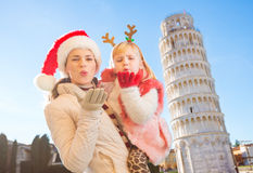 Mother in Christmas hat and daughter giving air kiss in Pisa Stock Photos