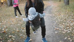Mother circling a little son in an autumn park. Happy family in autumn park. Happy family in nature concept in slow stock video footage