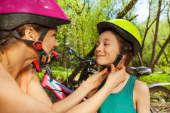 Mother clasping her daughter's bicycle helmet Stock Photos
