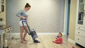 Mother clean dust from the floor with a vacuum cleaner and a little child`s daughter are playing near. stock video footage