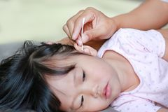 Mother Cleaning Baby Ear With cotton swab. royalty free stock photos