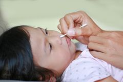 Mother Cleaning Baby Ear With cotton swab stock photo