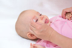Mother cleaning baby's eyes Royalty Free Stock Photo