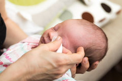 Mother cleaning eyes of a newborn baby Stock Image