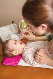 Mother cleaning mucus of baby with nasal aspirator Stock Images