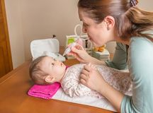 Mother cleaning mucus of baby with nasal aspirator. Mother cleaning mucus catarrh of adorable baby with a nasal aspirator Royalty Free Stock Images