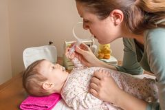 Mother cleaning mucus of baby with nasal aspirator. Mother cleaning mucus catarrh of adorable baby with a nasal aspirator Royalty Free Stock Image