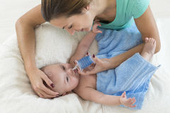 Mother cleaning nose mucus of adorable baby with a nasal aspirator Stock Photo