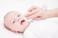 Mother cleans face of a newborn baby whith a cotton pad Royalty Free Stock Images