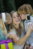 Mother Clicking Self Photo While Kids Kissing. Happy mother clicking self photo while kids kissing her on cheeks stock photography