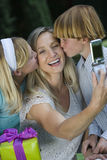 Mother Clicking Self Photo While Kids Kissing Stock Photo