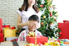 Mother closing eyses her sons with special gift place on table s stock images