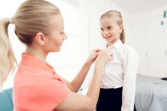 Mother collects her daughter to school. Mother helps dress a little girl. Stock Photo