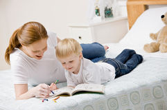 Mother coloring in coloring book with son. Devoted mother coloring in coloring book with son on bed in bedroom Royalty Free Stock Photography