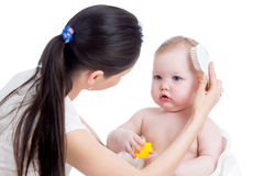 Mother combing baby`s hair after bathing Stock Images