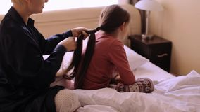 Mother combing daughter hair braids plait her stock video