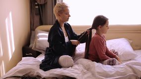 Mother combing daughter hair braids plait her stock video footage