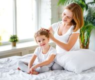 Mother combing hair daughter in bed Royalty Free Stock Photos