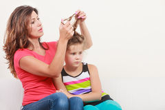 Mother combing hair for daughter Stock Photography