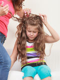 Mother combing hair for daughter Stock Images