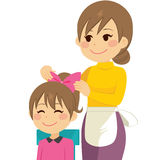 Mother Combing Hair. Happy young mother combing daughter hair with sweet face Stock Images