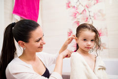 Mother combing hair of her daughter after taking bath Royalty Free Stock Photos