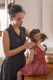 Mother combing the hair of her daughter stock images