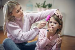 Mother combing her daughter at home. stock photography