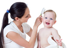 Mother combing kid's hair after bathing baby Royalty Free Stock Photos