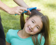 Mother Combs Girls Hair. A happy girl with long brown hair and brown eyes who just lost her two front teeth smiles as she sits on the grass and her mother combs Stock Photography