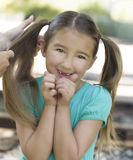 Girls Hair is Combed By Mother. A happy girl with long brown hair in pig-tails and brown eyes who just lost her two front teeth smiles as her mother combs her Stock Image