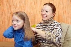 Mother combs the hairs of daughter. At home Royalty Free Stock Photos