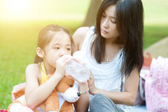 Mother comforting child and drinking water. Asian mother comforting her crying child in the park, Family outdoor lifestyle Royalty Free Stock Photo