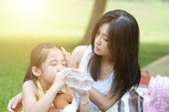 Mother comforting child. Portrait of Asian mother comforting her crying child in the park, Family outdoor lifestyle royalty free stock images