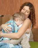 Mother comforting crying child. Crying child and his careful mom in home interior Royalty Free Stock Photo