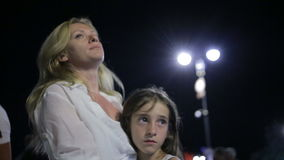 Mother comforting crying daughter outdoor. Mom and daughter at night