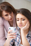 Mother Comforting Daughter Being Bullied By Text Message Stock Photos