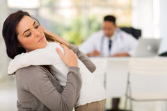 Mother comforting daughter. Caring mother comforting her ill daughter in doctor's office Royalty Free Stock Images